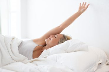 happy-young-woman-stretching-in-bed-after-sleep_1262-5199