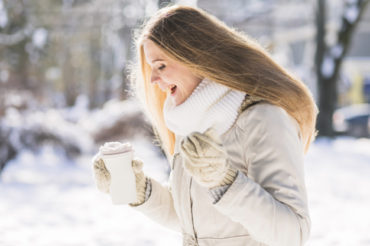 happy-female-veterinarian-holding-takeaway-coffee-cup-standing-in-snow_23-2147928548