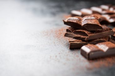 pieces-of-chocolate-on-a-wooden-table-and-cacao-sprinkled_1220-537